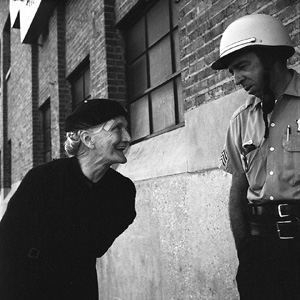 Woman and policeman by Vivian Maier